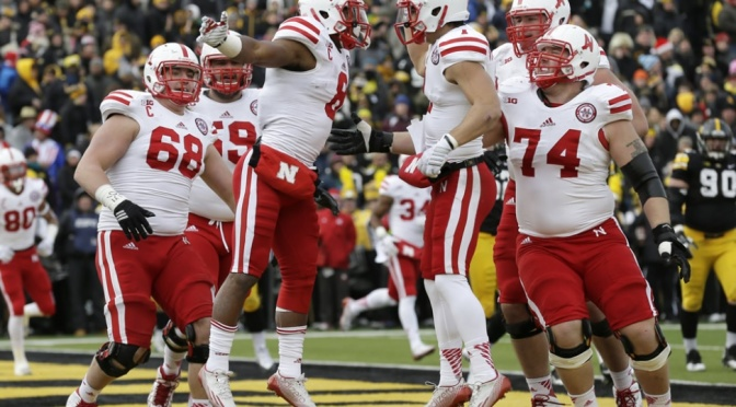 Nebraska running back Ameer Abdullah (8) celebrates with teammate Jordan Westerkamp after catching a 5-yard touchdown pass during the first half of an NCAA college football game against Iowa, Friday, Nov. 28, 2014, in Iowa City, Iowa. (AP Photo/Charlie Neibergall)