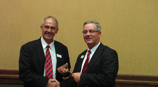 Dan Hughes accepts the gavel and position of chairman of US Wheat Associates from the former chairman Darrell Davis of South Dakota.