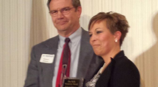RRN/ Lexington Area Chamber of Commerce Executive Director Tina Reil-Lux(right) presents the Jim Kelly Award to Richard Johnson at the Chamber's annual banquet on February 27, 2015.