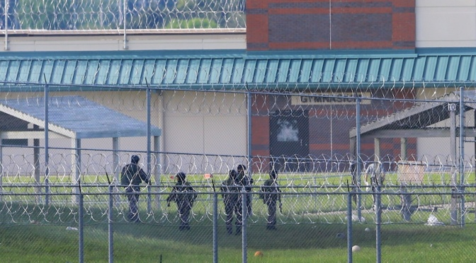 Armed personnel patrol the grounds of the Tecumseh State Correctional Institution, in Tecumseh, Neb., Monday, May 11, 2015. Two inmates were found dead Monday at the maximum security prison after officials regained control of the facility. Inmates took control of at least part of the Tecumseh State Correctional Institution Sunday during an incident when two staff members and two inmates were injured, according to the state Department of Correctional Services. (AP Photo/Nati Harnik)