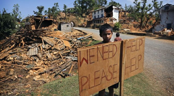 Courtesy/Associated Press/Manish Sarup. A Nepalese boy stands outside his village with a signboard asking for help in Pauwathok village, Sindhupalchok district, Nepal, Saturday, May 2, 2015. Life has been slowly returning to normal in Kathmandu, but to the east, angry villagers in parts of the Sindhupalchok district said Saturday they were still waiting for aid to reach them. In the village of Pauwathok, where all but a handful of the 85 houses were destroyed, three trucks apparently carrying aid supplies roared by without stopping.