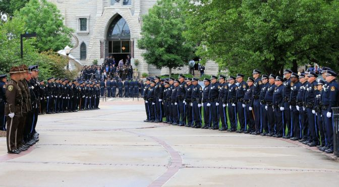 Courtesy/AP. An honor guard of police officers stands in front of St. John's Catholic Church on the campus of Creighton University during the funeral service of Omaha Police Officer Kerrie Orozco.