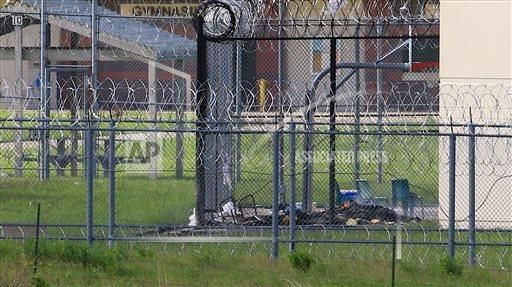 Courtesy/AP. A pile of smoldering rubbish is visible on the grounds of the Tecumseh State Correctional Institution, in Tecumseh.
