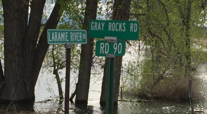 Road signs stand out on a flooded intersection near Fort Laramie .(Bill Boyer/KNEB)