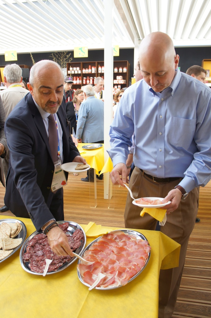 RRN's Jesse Harding. Governor Ricketts samples traditional products of aged salami and prosciutto with Coldretti member.