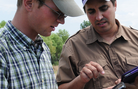 K-State's Ignacio Ciampitti (right) demonstrates the new soybean yield estimator app to Garrett Kennedy o