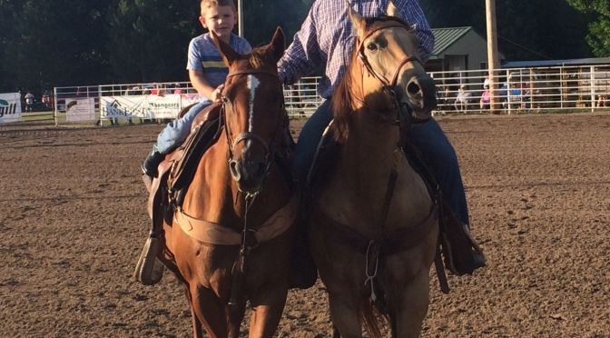 Courtesy/ Oregon Trail Rodeo.  Trevor Haake and his older son Hadley pose for the camera while on horseback. The Grand Island steer wrestler has a younger son, Ira, and will compete at the Oregon Trail Rodeo in Hastings this weekend.