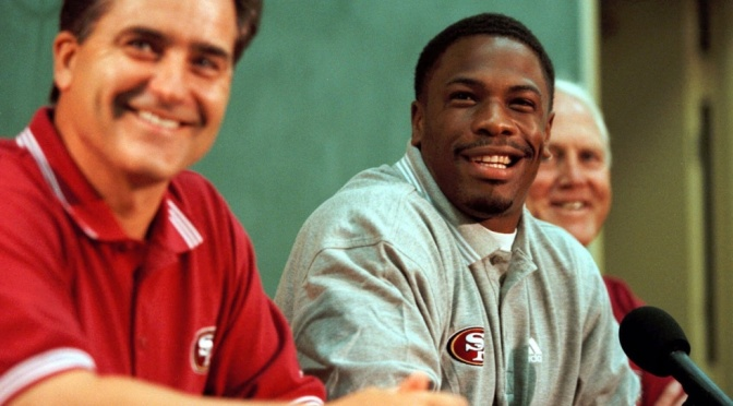 FILE - In this July 26, 1999, file photo, newly-signed San Francisco 49ers running back Lawrence Phillips, center, smiles with 49ers head coach Steve Mariucci, left, and general manager Bill Walsh during a news conference at training camp in Stockton, Calif. Phillips has been charged with murder in the death of his cellmate at a Central California prison. Phillips was once one of the nation's top college football players at Nebraska. He played for the St. Louis Rams, Miami Dolphins and San Francisco 49ers during a three-year NFL career. Phillips is serving a sentence of more than 31 years. He was convicted of choking his girlfriend and later of driving his car into three teens after a pickup football game.(AP Photo/Brian Baer, File)