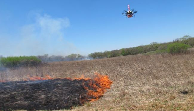 Courtesy/AP. A drone designed to ignite controlled grass fires comes in for a landing in a field at the Homestead Monument of America in Beatrice, Neb.,  University of Nebraska-Lincoln researchers are testing the drone as a possible tool for firefighters. (AP Photo/Grant Schulte)