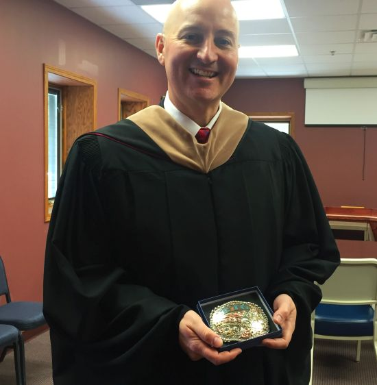 RRN/Gov. Pete Ricketts holds new personalized belt buckle that each NCTA graduate receives.