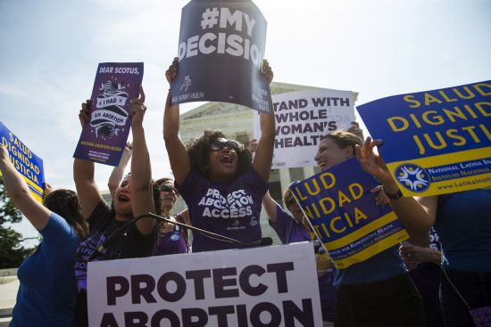 Courtesy/Associated Press. Pro-choice activists celebrate during a rally at the Supreme Court in Washington, Monday, June 27, 2016, after the court struck down Texas' widely replicated regulation of abortion clinics. The justices voted 5-3 in favor of Texas clinics that had argued the regulations were a thinly veiled attempt to make it harder for women to get an abortion in the nation's second-most populous state. (AP Photo/Evan Vucci)