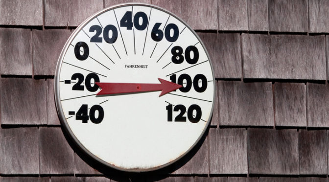 Thermometer Reading One Hundred Degrees On A Weathered Wall Of Wooden Shingles
