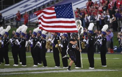 Northwestern wide receiver Austin Carr (80) carries the American flag before an NCAA college football game against Nebraska in Evanston, Ill.,  Saturday, Sept. 24, 2016. (AP Photo/Matt Marton)