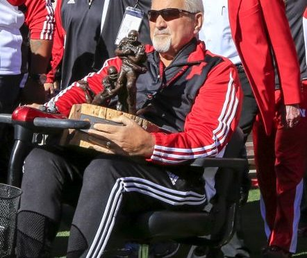 In this Oct. 24, 2015, photo, former Nebraska offensive line coach Milt Tenopir holds the 1996 Tostitos Fiesta Bowl trophy before an NCAA college football game against Northwestern, in Lincoln, Neb.  Tenopir, who coached some of college football's most dominant offensive lines with Nebraska in the 1980s and '90s, has died after a long battle with cancer. He was 76. Tenopir's daughter, Kim Lester, confirmed Tenopir's death Monday, Sept. 26, 2016.  Tenopir, who retired in 2003, was considered a guru of line play during his 29 years with the Cornhuskers. (AP Photo/Nati Harnik)