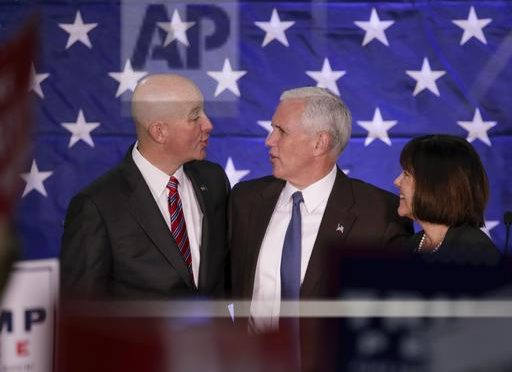 Republican vice presidential candidate Indiana Gov. Mike Pence and his wife Karen stand on stage with Nebraska Gov. Pete Ricketts, left, before speaking at a campaign stop in Omaha, Neb., Thursday, Oct. 27, 2016. (AP Photo/Nati Harnik)
