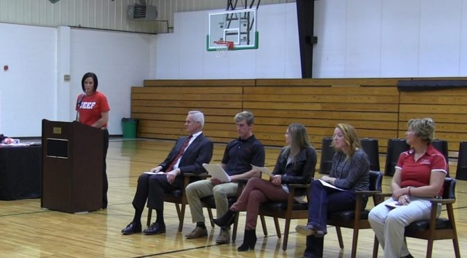 Loomis Public Schools Superintendent Nicole Hardwick addresses a school assembly Friday in Loomis as the school starts it's part of the Nebraska Beef in Schools program.  Among those in attendance were Lt. Gov. Mike Foley, seated next to the podium.  (RRN Image)