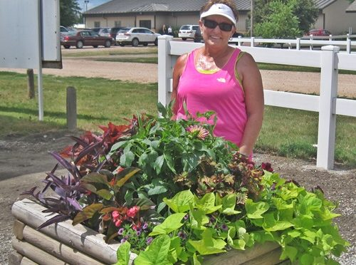 RRN/MJ Hart, Dawson County Fair Board Member and Master Gardener, standing next to one of her creations