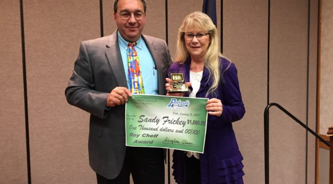 Board Governance Committee Chairman, Jim Lapaseotes  presenting the Roy Chelf Award to Sandy Frickey at Panhandle Coop's Annual Meeting.