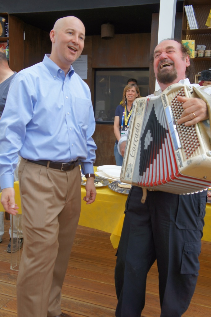 RRN's Jesse Harding. Governor Ricketts partakes in a tradition of singing with an accordionist.